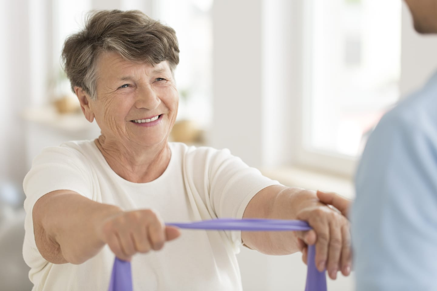 elderly-woman-using-resistance-band-to-stretch-arms