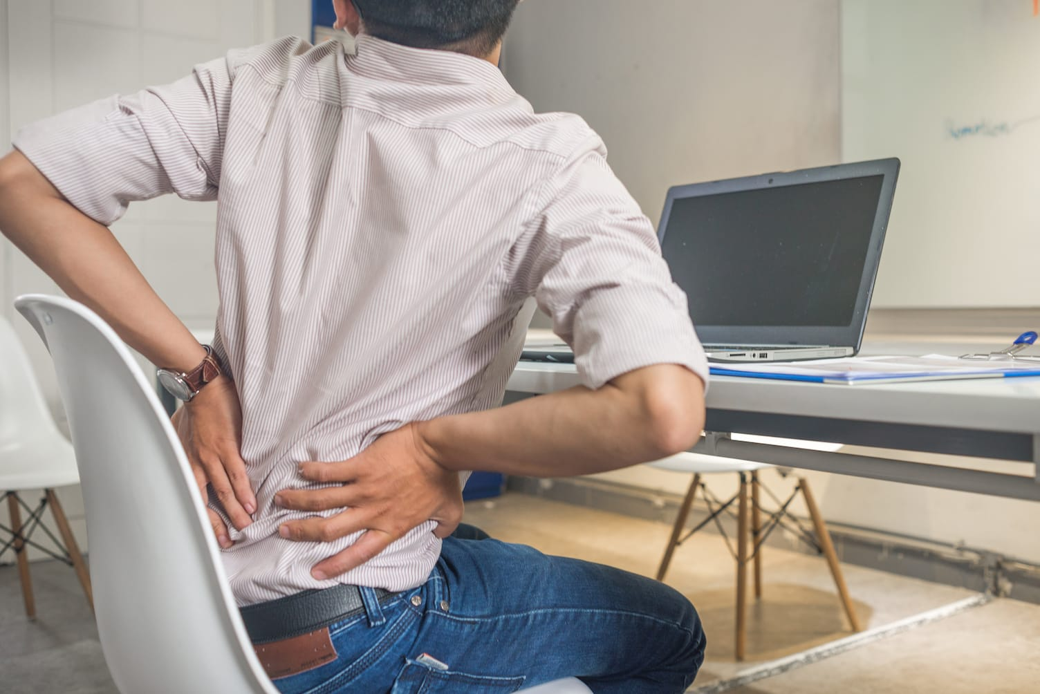 man-holding-his-back-in-pain-on-office-chair