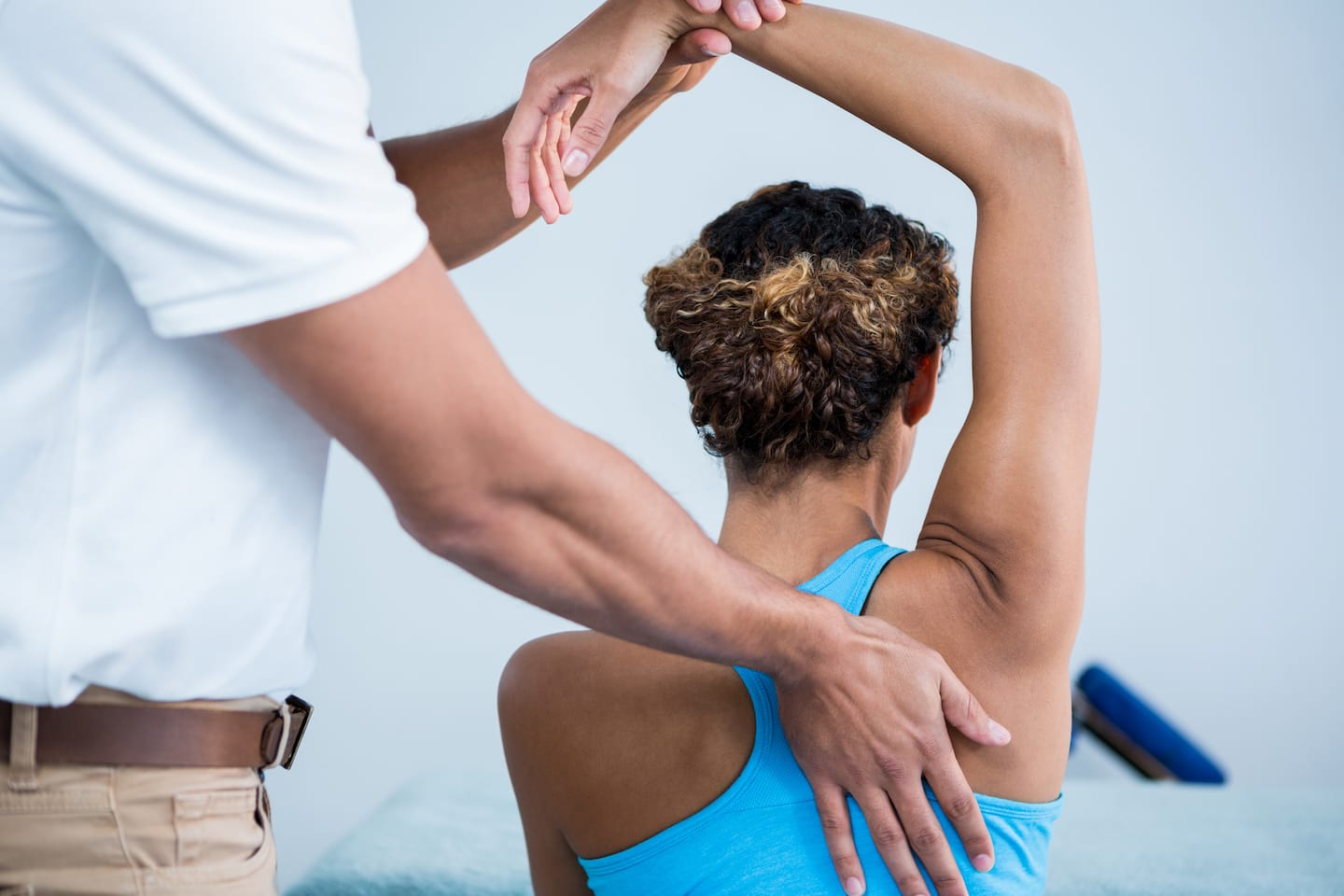 female-having-right-arm-stretched-by-physiotherapist